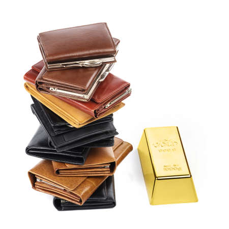 Lot of leather wallets and gold bar on white background Reklamní fotografie