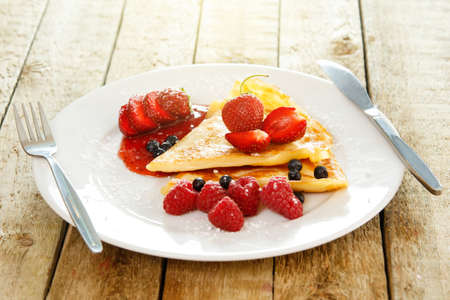 Pancakes with berries and sugar powder on wooden table Stock Photo