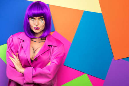 Model in creative image with pop art makeup against colorful background