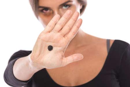 Mujer con un punto negro en la palma da una señal sobre la violencia doméstica