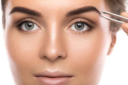 Zbliżenie kobiecej twarzy i brwi za pomocą pęsety