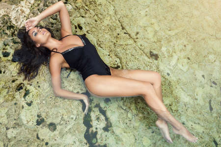 Sexy woman wearing black swimsuit is lying in the water
