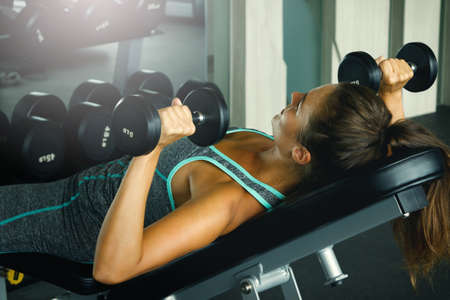 Young and beautiful woman working out with dumbbells in gym