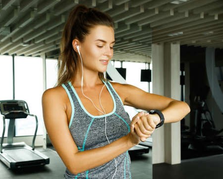 Woman using smart watch in the gym during her workout Stock Photo