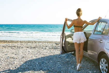 Happy and carefree woman in the car on the beach Stock Photo