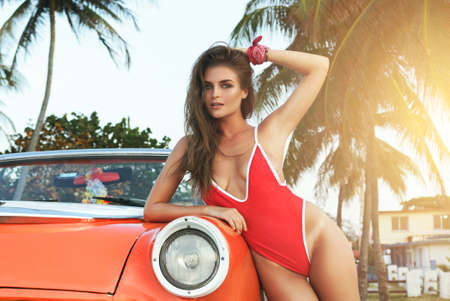 Sexy woman in red swimsuit and retro cabriolet car on the beach