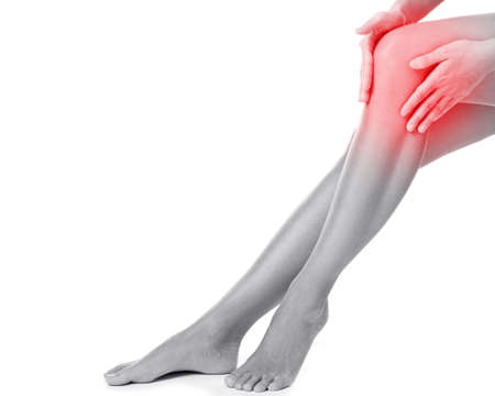 Woman with pain in her knee on white background 版權商用圖片