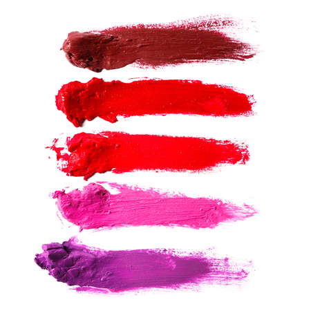 Different multi colored samples of a smudged lipstick over white background