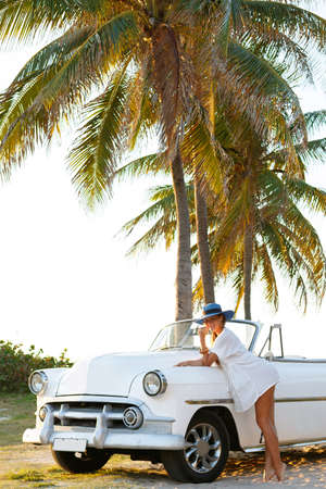 Beautiful woman in blue hat and white retro cabriolet on the beach Banco de Imagens
