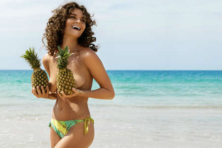 Beautiful woman with curly hair is holding pineapples  on the beach 스톡 콘텐츠