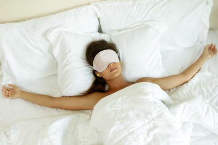 Woman is wearing eye mask and using earplugs for better sleeping Stockfoto