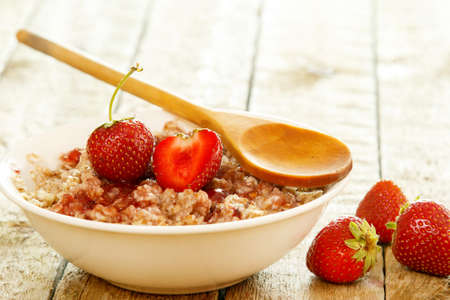 Cooked oatmeal, berries and strawberry jam on wooden table 写真素材