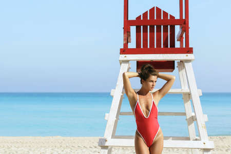 Sexy woman in red swimsuit posing beside a lifeguard tower Stock Photo