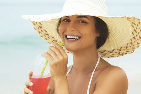 Woman in beach hat with a glass of cocktail on the beach Banco de Imagens