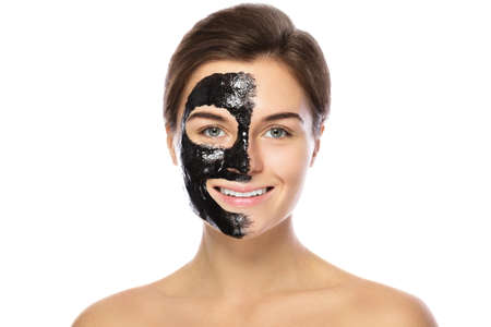 Beautiful woman with a purifying black mask on her face. Isolated on white background