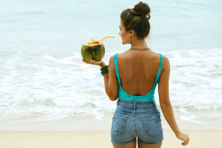 Happy woman with a coconut drink on the beach Banco de Imagens
