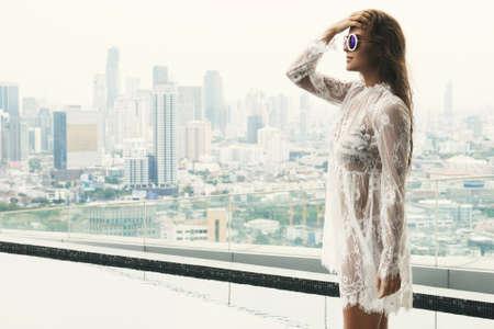 Woman in beautiful lace dress beside rooftop pool Banco de Imagens