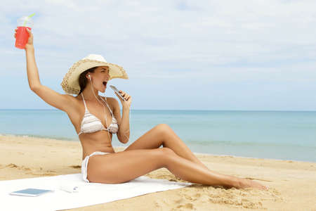 Cheerful woman listening music and sings on the beach Banco de Imagens