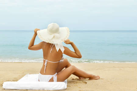 Woman in hat is relaxing on the beach