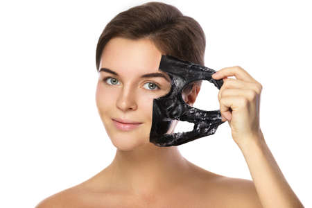 Beautiful woman is removing purifying mask from her face over white background