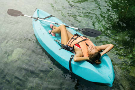 Happy woman relax during lying in the kayak