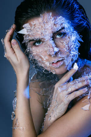 Female face covered with a lot small pieces of glass. Realistic visual effects made of silicone gel. Banco de Imagens