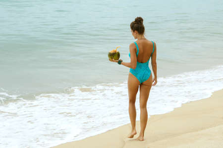 Happy and beautiful in swimsuit with a coconut on the beach