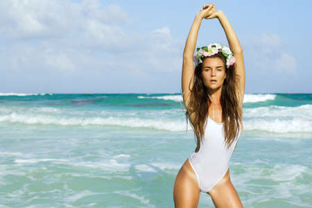 Sexy woman in white swimsuit is posing on the beach Banco de Imagens