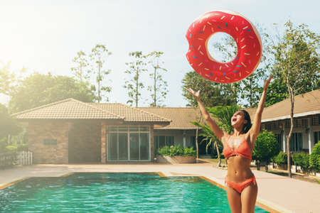 Sexy woman is wearing knitted bikini and holding inflatable swim ring in shape of donut