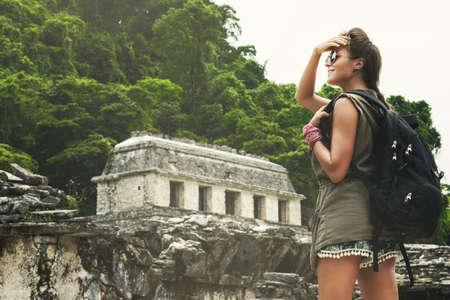Hiker woman with backpack looking at ancient Mayan ruins Banco de Imagens