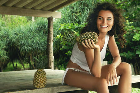 Beautiful woman with curly hair and pineapple
