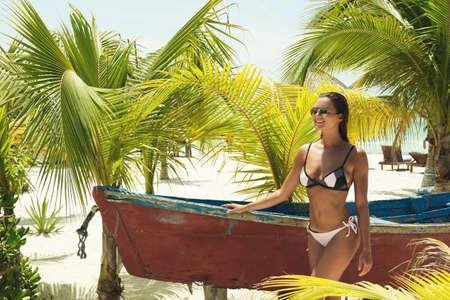 Beautiful woman in bikini and sunglasses beside a old boat