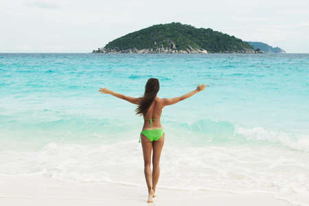 Happy woman in green crochet bikini on the beach. Beach holidays beside the sea. Banco de Imagens