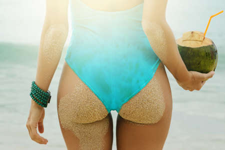 Female buttocks and coconut drink on the beach
