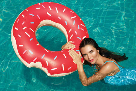 Beautiful woman and inflatable swim ring in shape of a donut in the pool