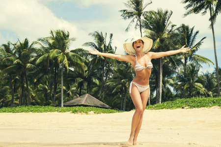 Happy woman wearing bikini and hat on the beach with a palm trees on background