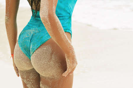 Sexy female buttocks covered with sand on the beach