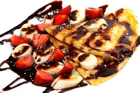 Pancakes with strawberry, banana and chocolate syrup on white background