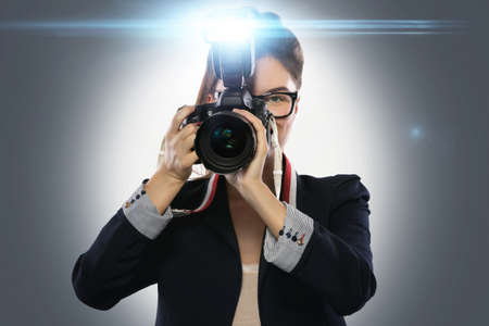 Woman photographer with a DSLR camera isolated on white background