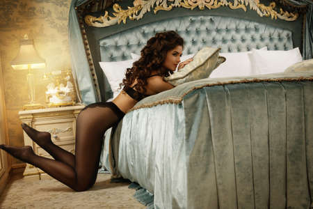 Sexy woman wearing a beautiful lingerie and a black tights in the luxury bedroom