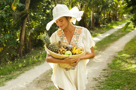 Beautiful woman wearing broad-brim hat in the tropical garden with a basket of fresh fruits