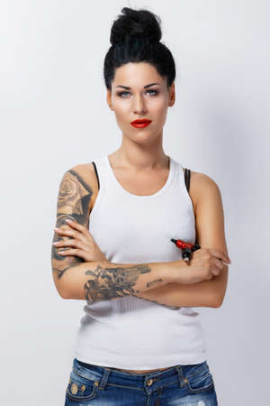 Young woman tattooist with a tattoo-machine in her hand on white background