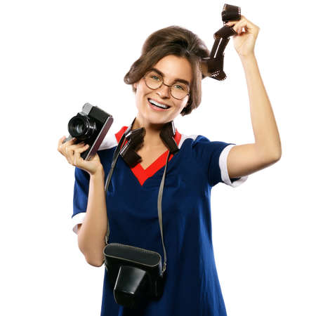 Woman in vintage look holding camera and photographic film in her hands isolated on white background