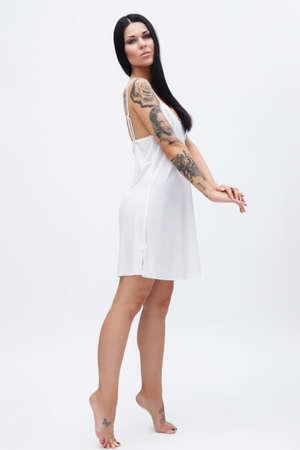 Woman with tattoos wearing beautiful nightgown