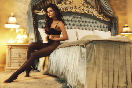 Sexy woman wearing a beautiful lingerie and a black tights in the luxury bedroom. Image taken with long shutter speed and mixed light for shaking artistic effect.