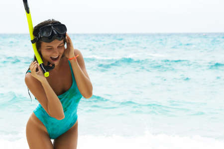 Happy and beautiful woman on the beach with mask for snorkeling