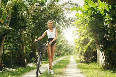 Sexy and beautiful woman with bicycle at hot summer day