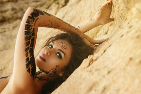 Beautiful woman with trace of car tire on her body is posing beside the sand cliffs