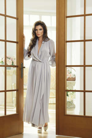 Gorgeous woman in beautiful silk dress standing beside a big doors in the bright room