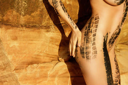 Female body with trace of car tire on her body beside the sand cliffs